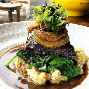 red wine braised beef cheek, seeded mustard mash, spinach, fried onion rings