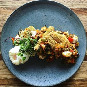 Crumbed sardines with caponata, pine nuts, baked ricotta and a poached egg