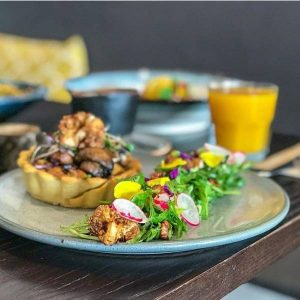 winter tartlet, vegan mushroom and roasted cauliflower tart comes with a mizuna, candied walnut and radish salad with truffle dressing.